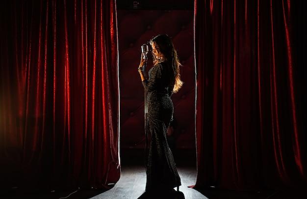 マイクを使ってポーズをとって黒いドレスの若い美しい歌手