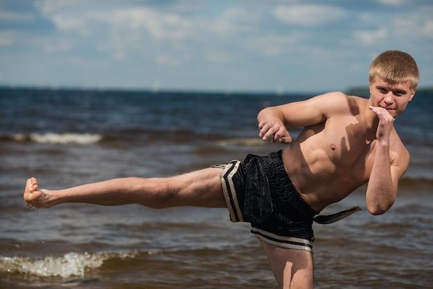 キックボクサーは海に対して夏に戸外で蹴る