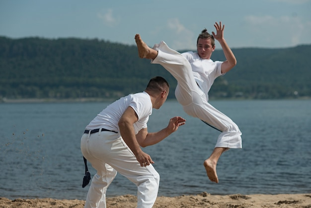 男性がビーチでカポエイラを訓練
