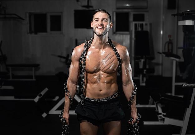 Мускулистый мужчина раб в цепях в спортзале, заключенный