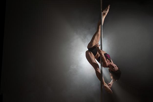 パイロンと美しいスリムな女の子。女性ポールダンサーの踊り