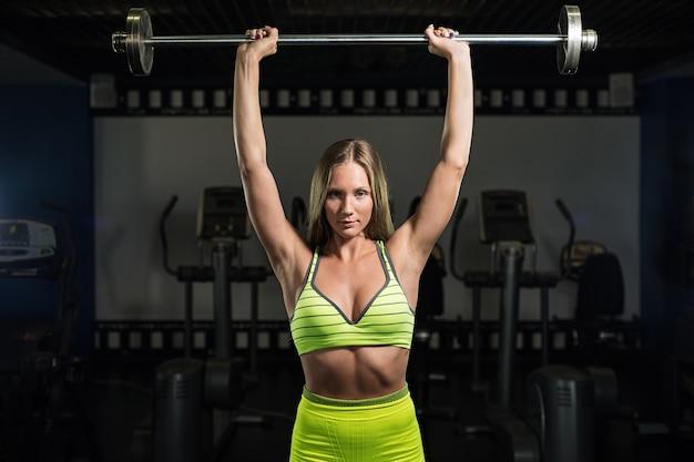 美しいセクシーな運動筋肉の若い女の子。フィットネス女の子がジムでトレーニング、バーベルでのエクササイズ