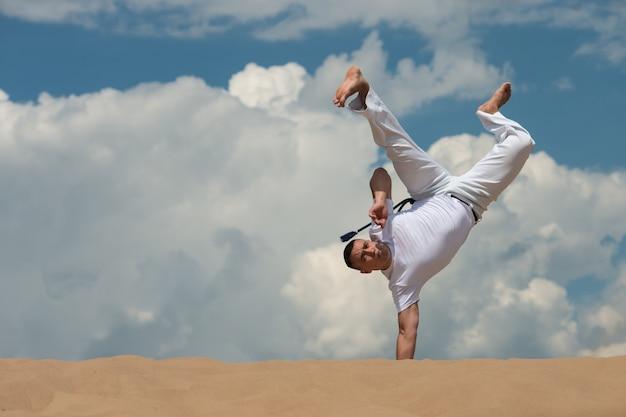 若い男がカポエイラを空に対して訓練します。男がアクロバティックなトリックを実行
