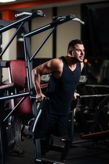 Мускулистый мужчина во время тренировки в тренажерном зале тренирует трицепс на брусьях