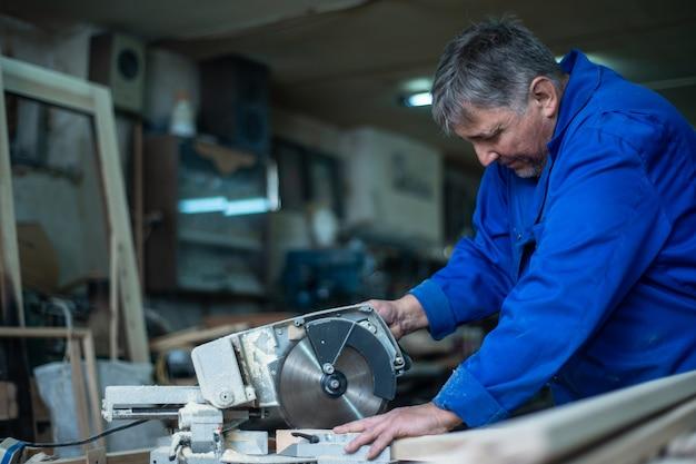 Электропила для распиловки досок, рабочий распиливает деревянную доску в мастерской