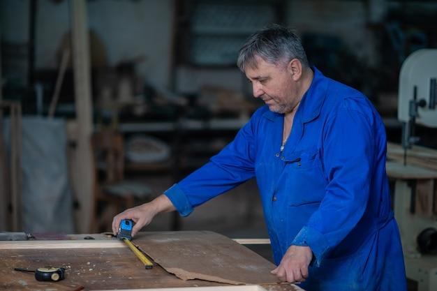 接着剤やさまざまなツールを使用してワークショップで大工のテーブルの上の木枠を組み立てる