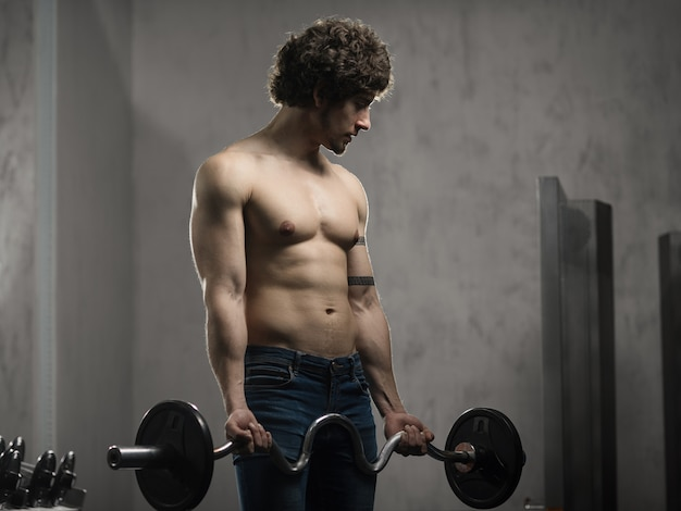 筋肉男はジムでバーベルと上腕二頭筋を訓練、手のトレーニング