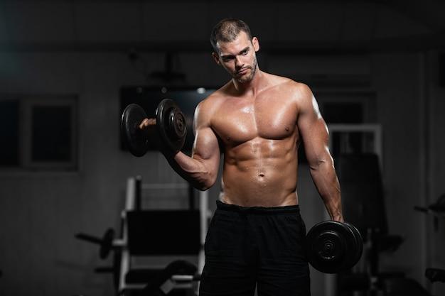 男はジムでトレーニングします。運動男はダンベルでトレーニングし、彼の上腕二頭筋をポンピング