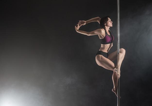 パイロンと美しいスリムな女の子。黒で踊る女性のポールダンサー