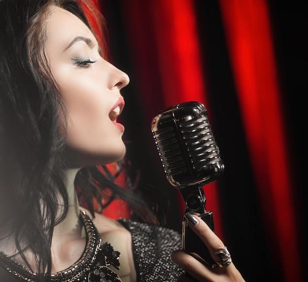 Портрет красивой женщины, поющей в микрофон