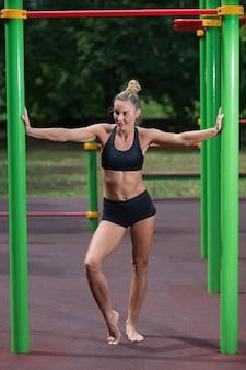 Девушка делает упражнения на турнике. женщина занимается тренировками