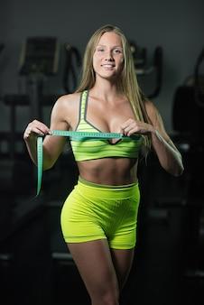 ルーレットを持つフィットネス女性は、胸部の周囲を測定します
