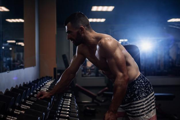 筋肉の若い男がジムでダンベルで背中を鍛える