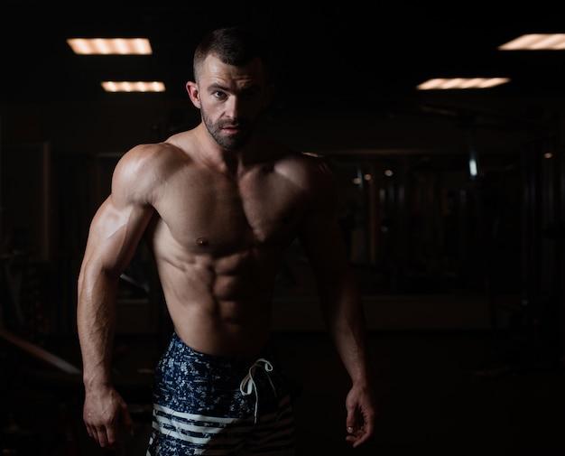 筋肉の体を持つ運動男はジムでポーズをとって、彼の筋肉を披露します。