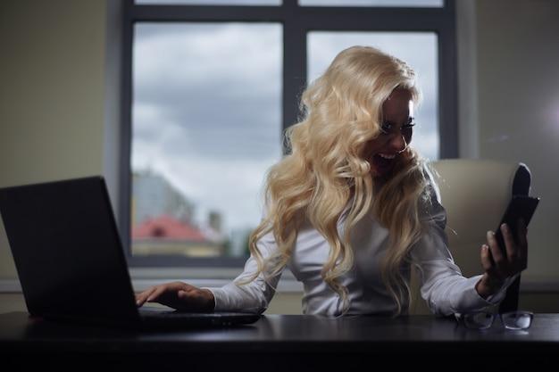 オフィスの魅力的な従業員は、テーブルに座って電話で誓います。負の感情