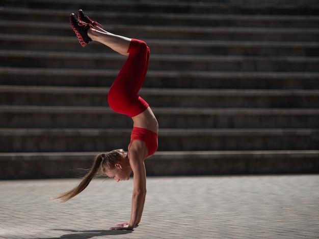 若い魅力的な女性は屋外でヨガを練習します。女の子は逆さまに逆立ちをします
