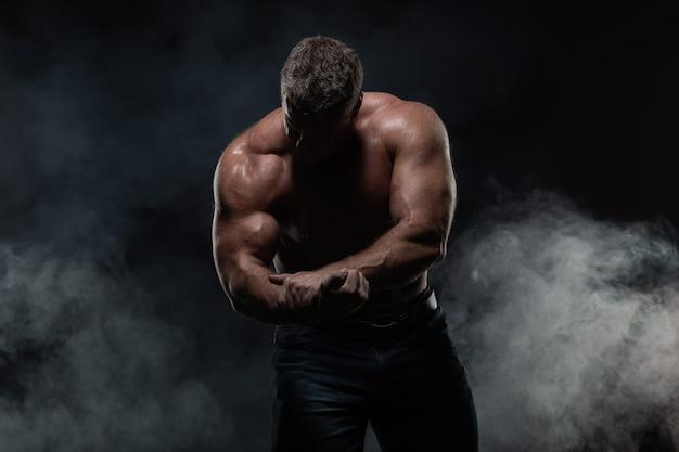 強力な筋肉男は黒の上腕二頭筋を示しています。強度とフィットネスの概念