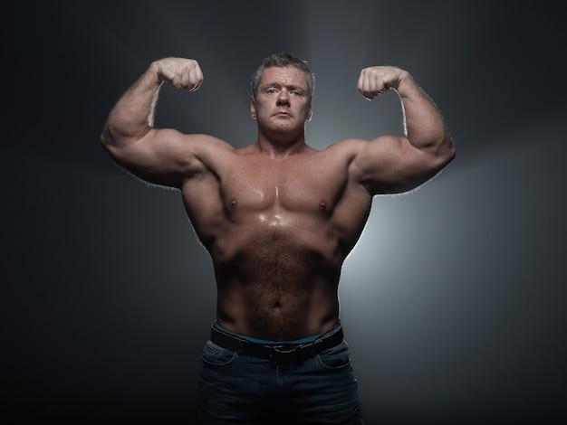 黒でポーズをとって強力な筋肉ボディービルダー。強さと健康の概念
