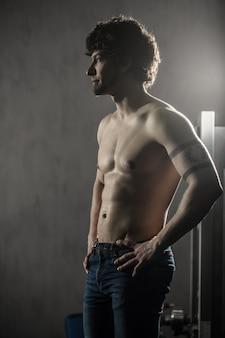 運動、男性のポーズの後ジムで休んで若い魅力的な男