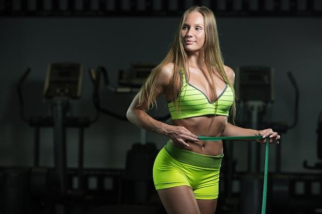ルーレットでフィットネス女性は腹部の周囲を測定します