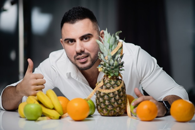 新鮮な果物が横たわっているテーブルに座って魅力的な男性。