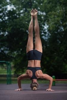 スポーツアクロバット少女は彼女の手の上に立って、アクロバティックな要素を作る