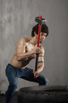アスレチック男がタイヤを打つ-ジムでハンマーでトレーニング