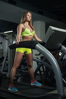 Красивая сексуальная спортивная мышечная молодая девушка. фитнес девушка тренируется в тренажерном зале, девушка отдыхает после тренировки.