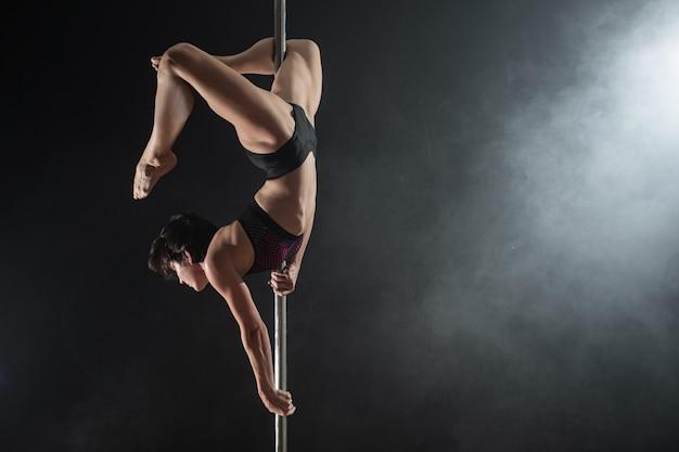 パイロンと美しいスリムな女の子。黒の背景に踊る女性のポールダンサー