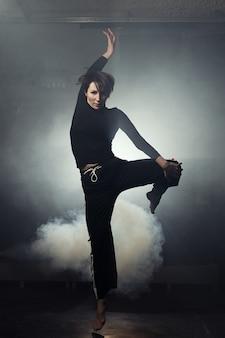 Современная красивая танцовщица в черной одежде позирует