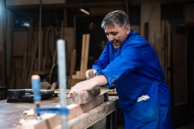Плотник работает в мастерской, рабочий строгает дерево с помощью строгального станка