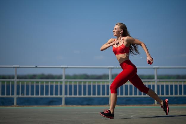 海岸で走っている若いフィットネス女性。健康的なライフスタイルの概念