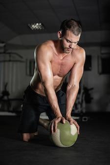 Фитнес-мужчина делает отжимания на мяче