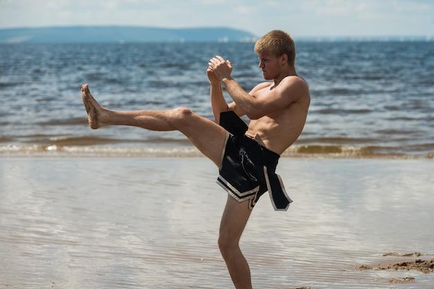 キックボクサーは夏に海に対して屋外で蹴ります。