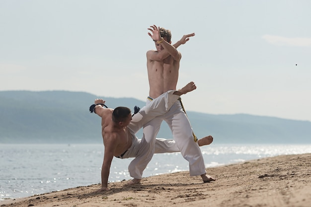 Мужчины тренируют капоэйру на пляже - понятие о людях, образе жизни и спорте.