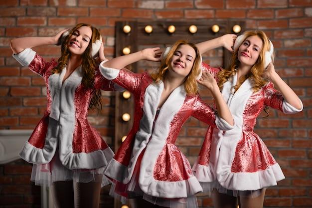 Трио новогодних персонажей снегурочки слушает музыку в наушниках
