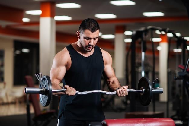 男はジムで上腕二頭筋を訓練します。筋肉ボディービルダー男はバーベルでのエクササイズ。