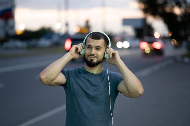 ヘッドフォンを持つ男は、街の通りで夜遅くに音楽を聴きます