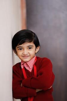Индийская маленькая девочка в школьной форме и показывая выражение
