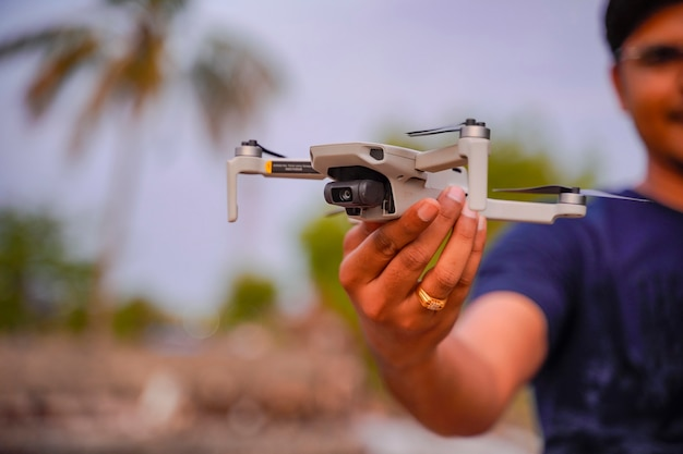 空を背景に手でドローンヘリコプター。手にデジタルカメラが付いているリモート制御ヘリコプター。閉じる。航空写真とビデオのための新しいツール。