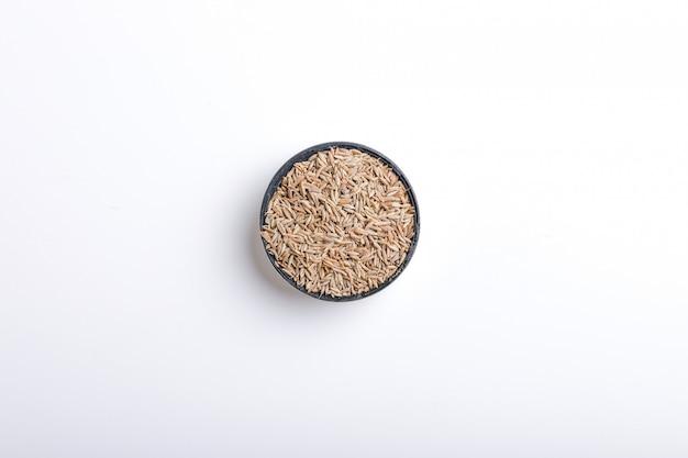 白い背景の上のボウルに乾燥クミンのヒープ