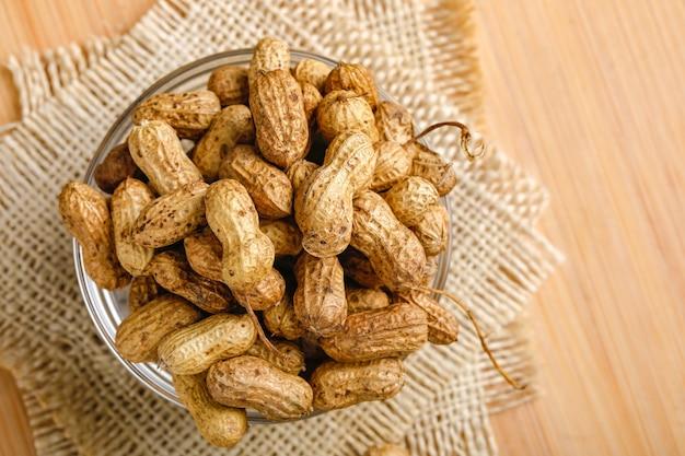 木製の背景上にボウルにピーナッツ。
