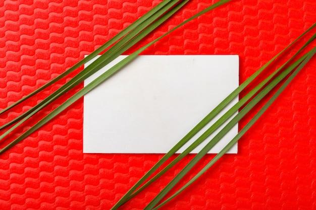 コピースペースを持つ赤い背景の上の花と葉