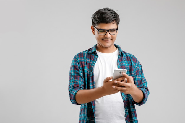 Молодой индийский мужчина с помощью смартфона