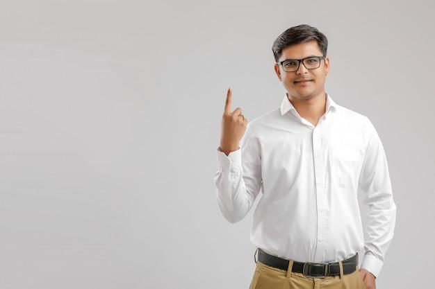 Молодой индийский мужчина показывает пальцем