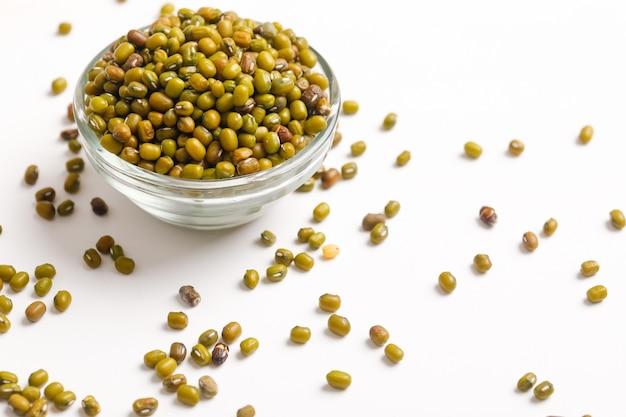 白のボウルに緑のグラム種子または緑豆