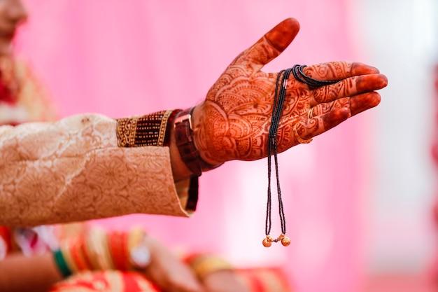 Мангасутра держит в руке жениха