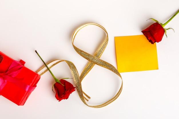 母の日の概念、赤いバラとコピースペースとゴールデンリボン。