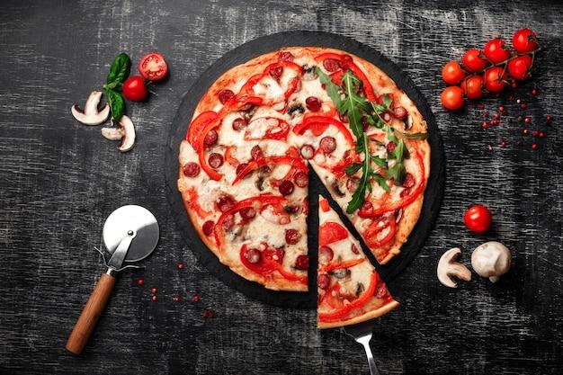 スモークソーセージ、チーズ、マッシュルーム、チェリートマト、ピーマンとヘラでピザのスライス