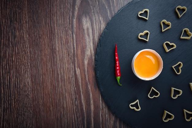 Разбитое яйцо красный перец на черном фоне